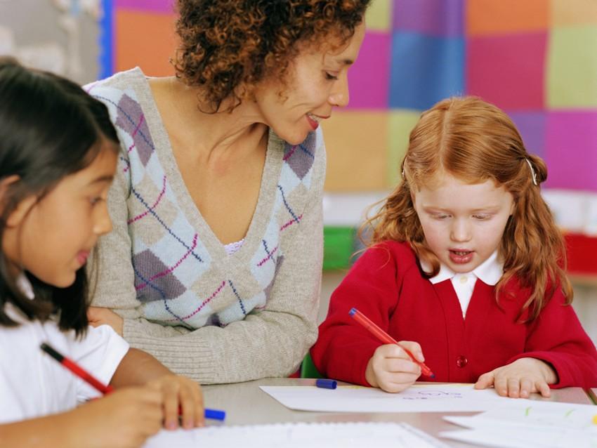 Teacher sitting at table watching schoolgirl (5-7) writing