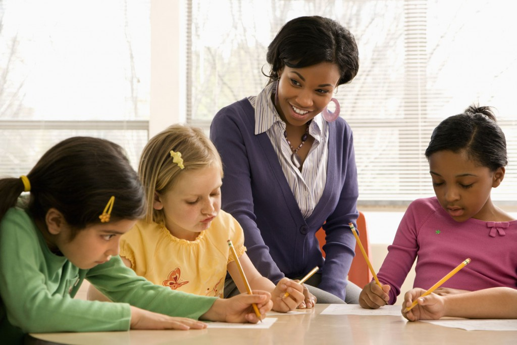 Teacher helping students in school classroom. Horizontally framed shot.